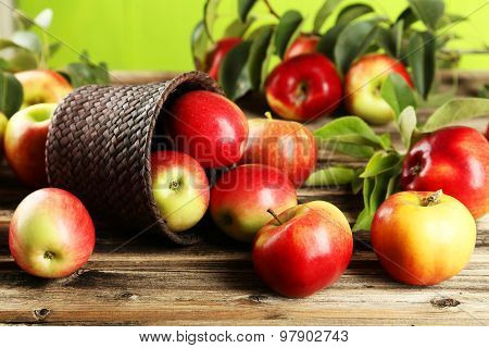 Apples in basket on wooden background