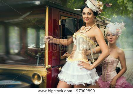 women posing over retro car