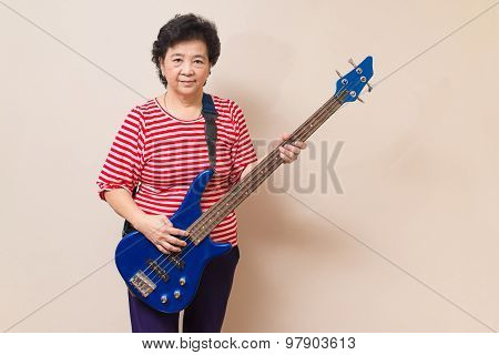Portrait Of Adult Asian Woman With Electric Bass On Reddish Yellow Gray Wall Background