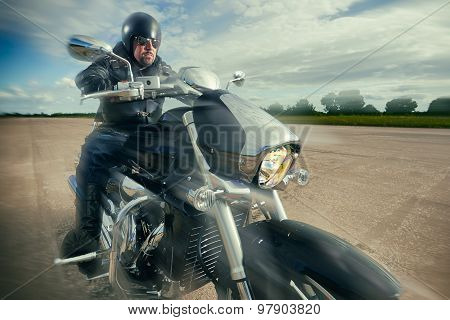 Biker in helmet and leather jacket racing on the road on a motorcycle.