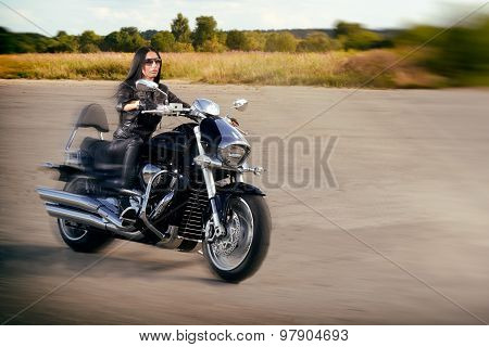 Biker girl in leather jacket riding on a motorcycle.