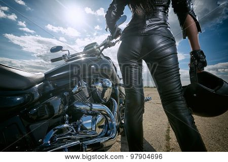 Biker girl in leather jacket standing by a motorcycle