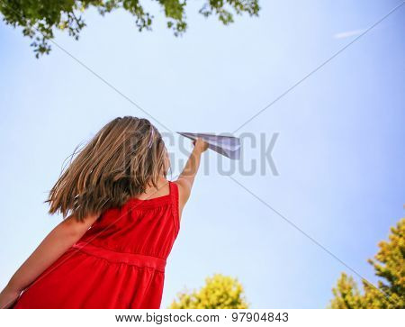 a cute toddler girl in a red dress throwing a paper airplane into the sky while a real plane is passing overhead in a park during summer time
