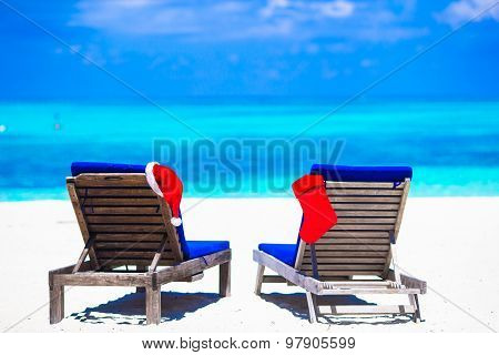 Red Christmas stocking and Santa Hat on beach loungers