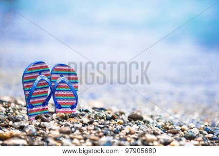 Kids flip flops on beach in front of the sea