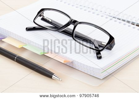 Office table with glasses over blank notepad
