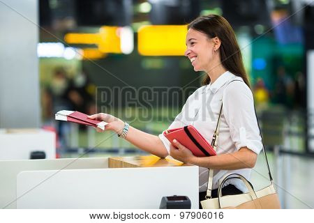 Young girl with passports and boarding passes at the front desk at international airport