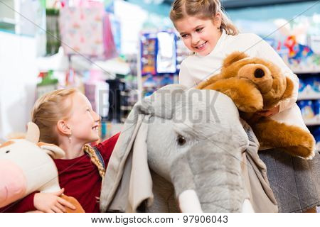 Two kids with stuffed elephant in toy store playing