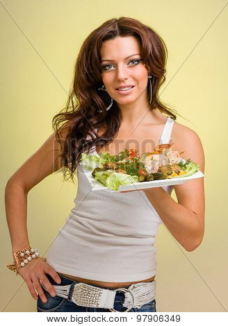 Waiters carrying hold  plates with meat on yellow background