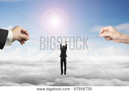 Businessman Hanging On Tightrope With Man And Woman Hands Holding