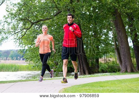 Woman and man jogging on dirt path in the woods together