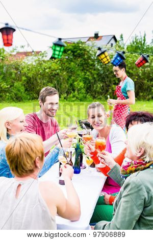 People toasting at party, in the background man at bbq grill with beer bottle in hand