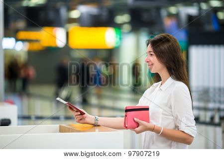 Beautiful woman with passports and boarding passes at the front desk at airport
