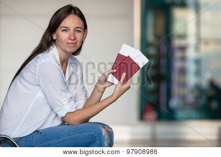 Happy young woman with air ticket and passports at airport waiting for flight