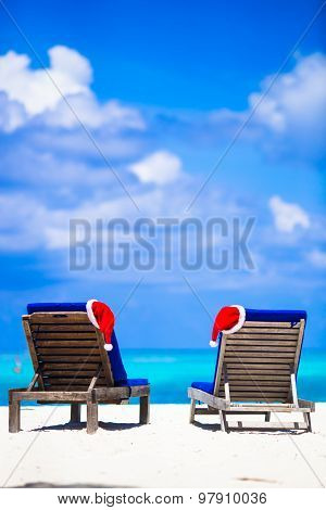 Christmas tropical concept: beach loungers with red Santa Hats