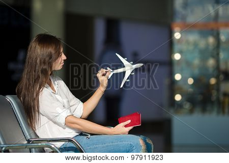 Pretty young female passenger with small model airplane at the airport