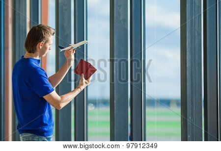 Young caucasian man holding passports and boarding pass at airport near window