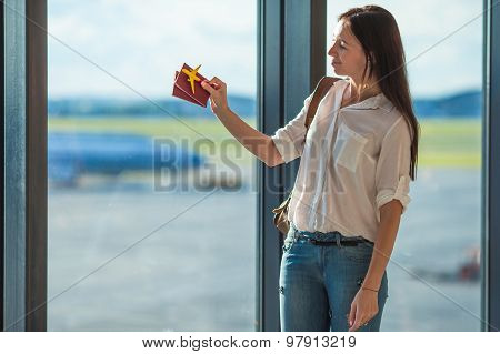 Happy young woman with passports and airplane model at airport