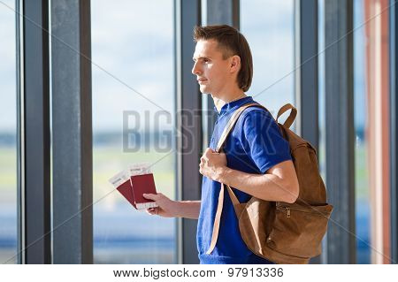 Young man holding passports and boarding pass at airport