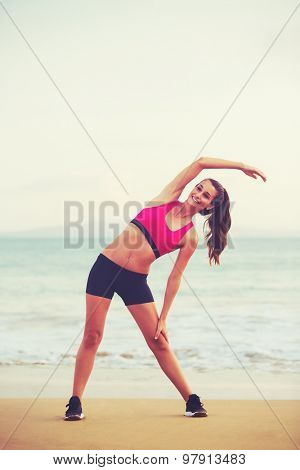 Young attractive fitness woman stretching on the beach at sunset. Healthy Active Lifestyle.