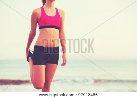 Healthy Active Lifestyle. Young fitness woman stretching and preparing for workout on the beach at sunset.