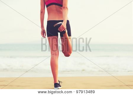 Healthy Active Lifestyle. Young fitness woman stretching on the beach at sunset.