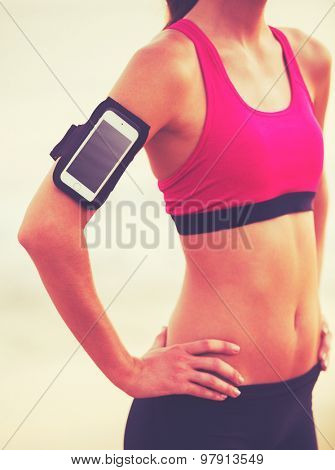 Active Healthy Sports Lifestyle with Modern Technology. Young attractive fitness woman with smart phone ready for workout.