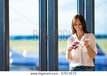 Pretty young girl with small model airplane at the airport