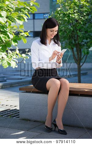 Business Woman Using Smartphone In City Park