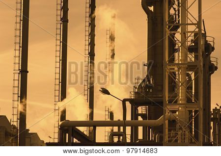 oil industry refinery, pipes and chimneys at sunset