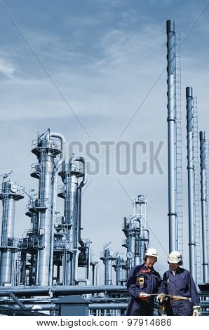 oil and gas workers with large refinery industry in background