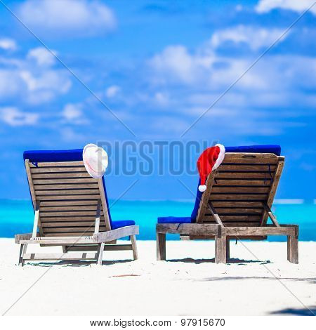 Christmas concept: beach loungers with red Santa and straw hats background beautiful turquoise sea