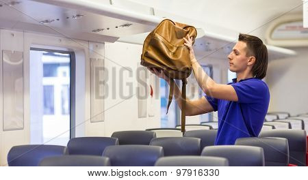 Young caucasian man putting luggage on the top shelf at train