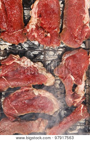 fresh raw beef meat fillet mignon on black grill grid over charcoal on brazier