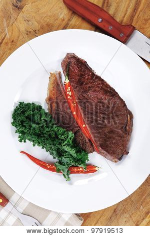 grilled beef steak fillet meat with red hot pepper and  raw kale leaf with ketchup sauce served on white plate over wood table