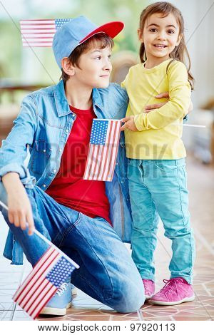 Happy siblings with American flags