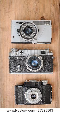 Three Retro Cameras On Wooden Background