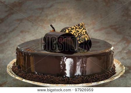 Ornate chocolate cake over dark slate background.