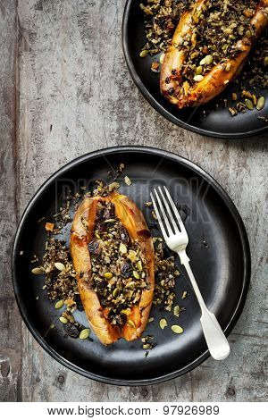 Baked sweet potato or yam, stuffed with wild rice, pepitas, and cranberries.  Overhead view, rustic wood background.