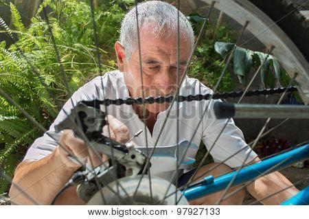Elderly Man  Repairing A Bicycle