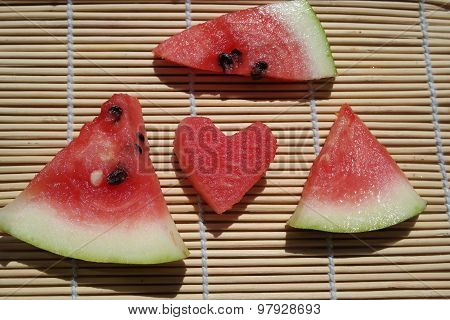 Watermelon Slices on wooden table. Watermelon cut in the shape of hearts ** Note: Shallow depth of f