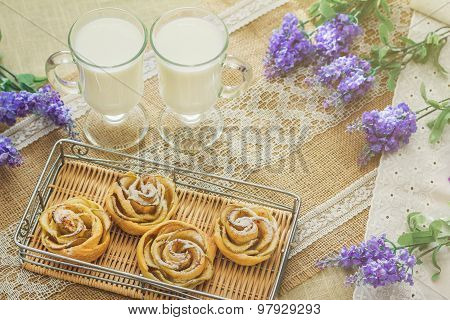 Breakfast with tasty homemade apple cakes and milk over sackcloth background in provence style