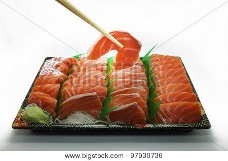 Chopsticks pinch fresh salmon sushi and wasabi