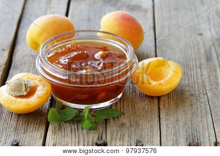 Apricot peach jam in a glass jar on a wooden background