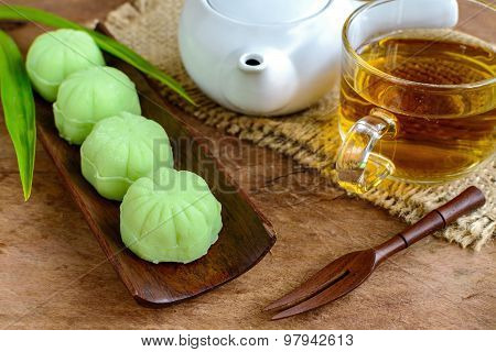 Greentea Mochi Flavored With Bean Filling And Cup Of Tea On Wooden Table