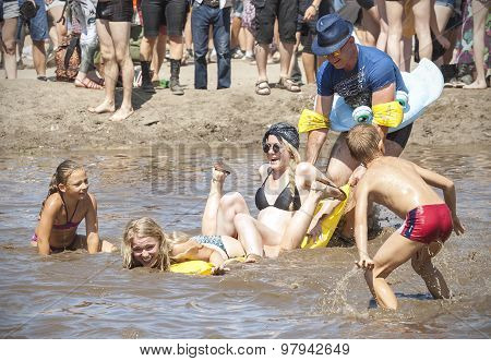 People Playing With Children In Mud Pool.