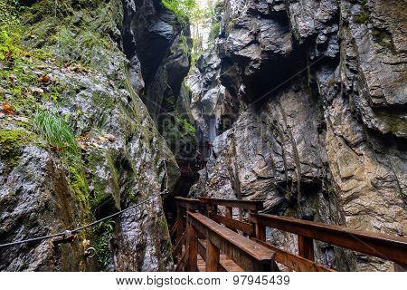 A Wooden Bridge Along A Vertical Cliff Over The Precipice.
