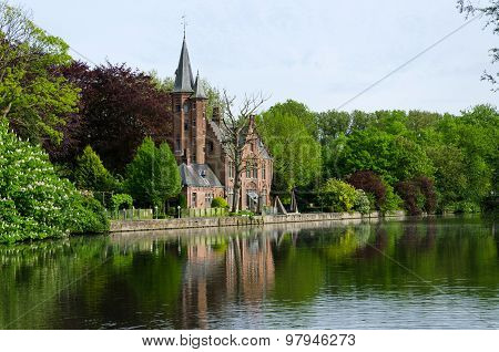 Flemish Style Castle Reflecting In Minnewater Lake In Bruges