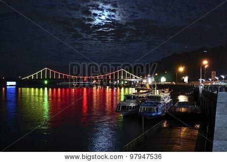 Kiev River Port And Pedestrian Bridge (the Park Bridge) At Night
