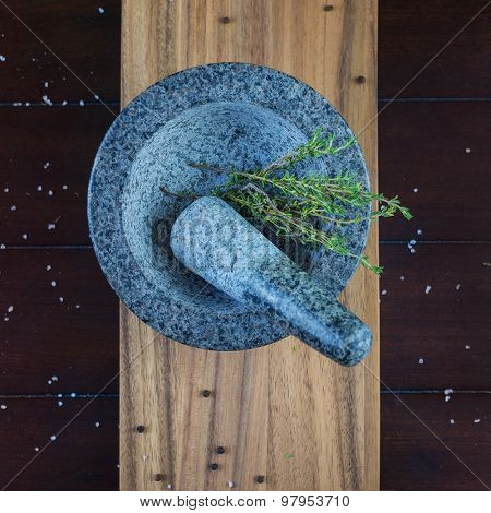 Granite stone mortar and thyme herb over wooden plank